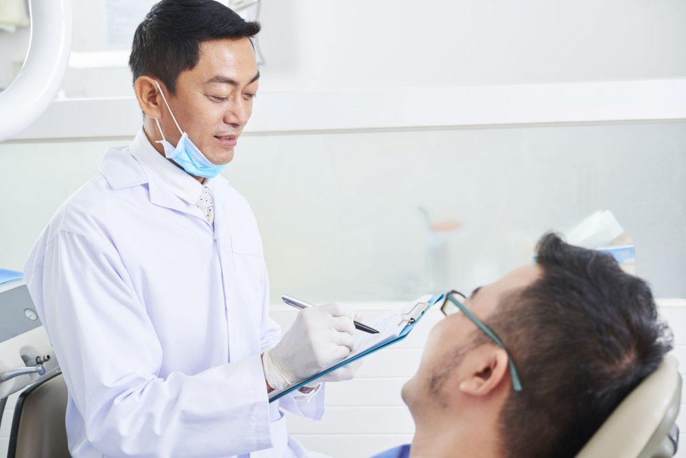 asian-male-dentist-at-work-D9DE6XX